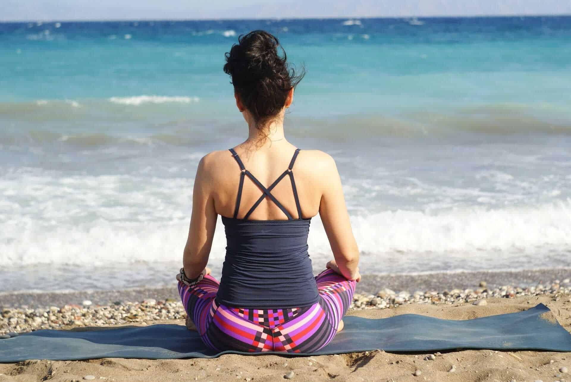 woman meditating near beach